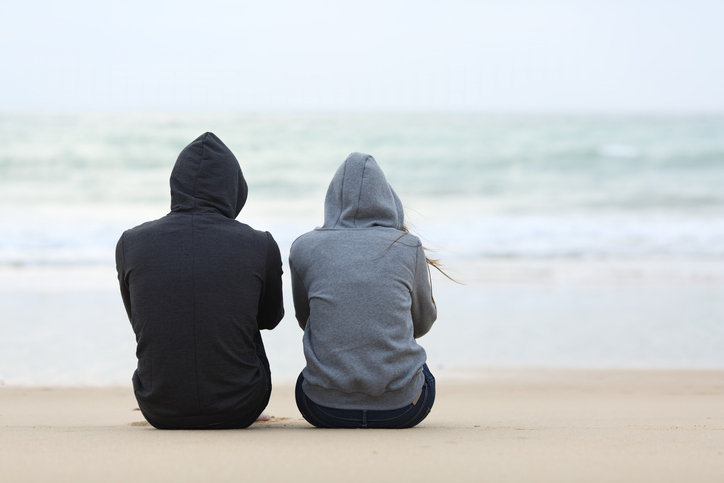 A drug addicted man sits with his girlfriend on the beach