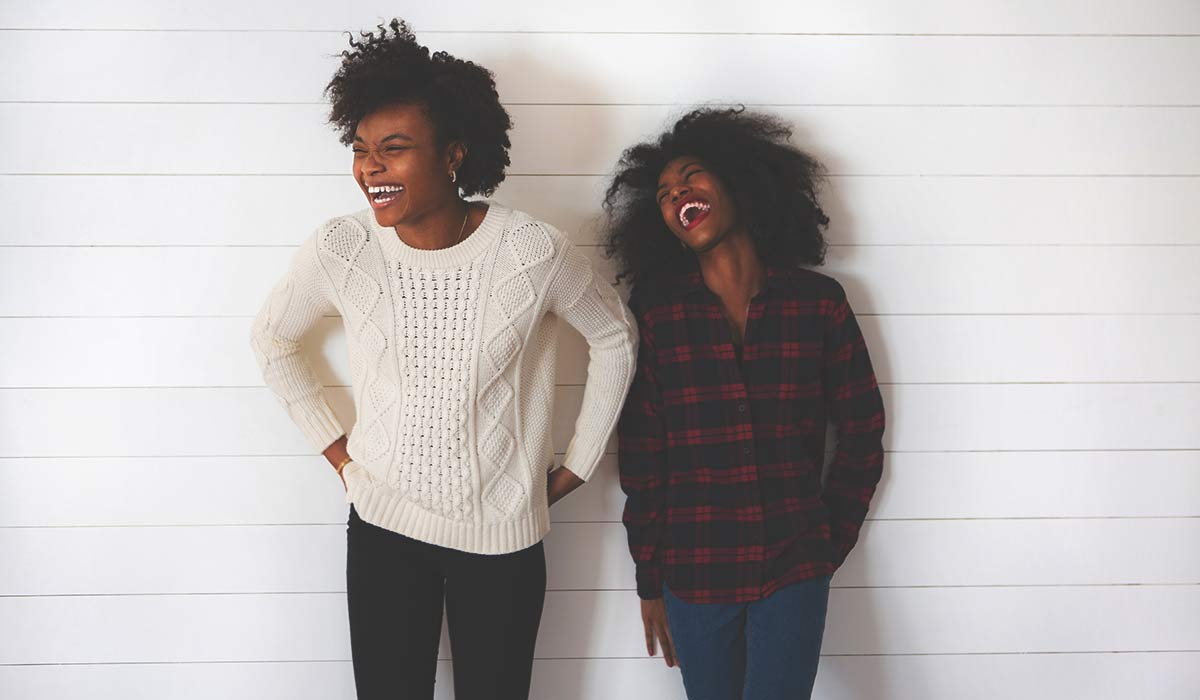 two women laughing against a white wall